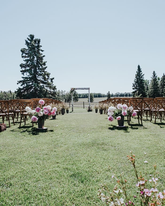 down the aisle view peony flowers rustic chairs outdoor ceremony wedding