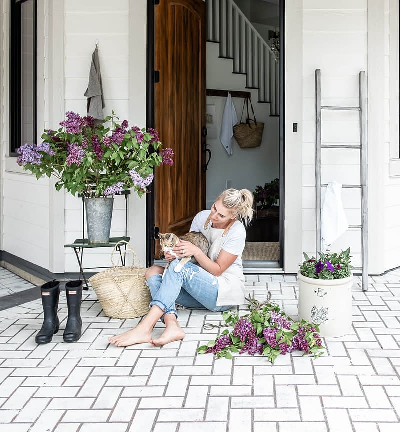 Brittany Hislop on front step with purple lilacs