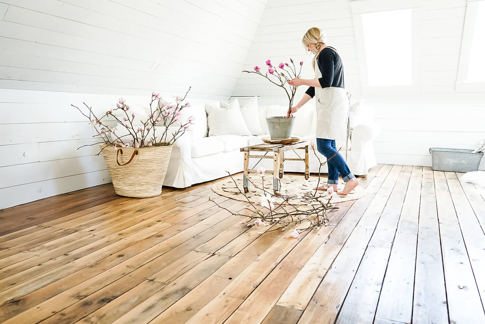 girl decorating with magnolia in a shiplap attic for a photo shoot