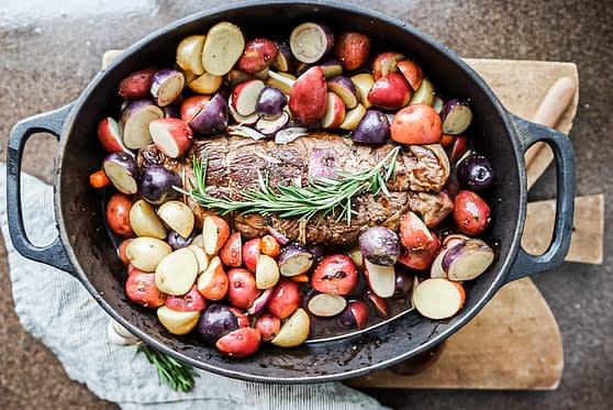 roast beef and potatoes in the pot ready to cook