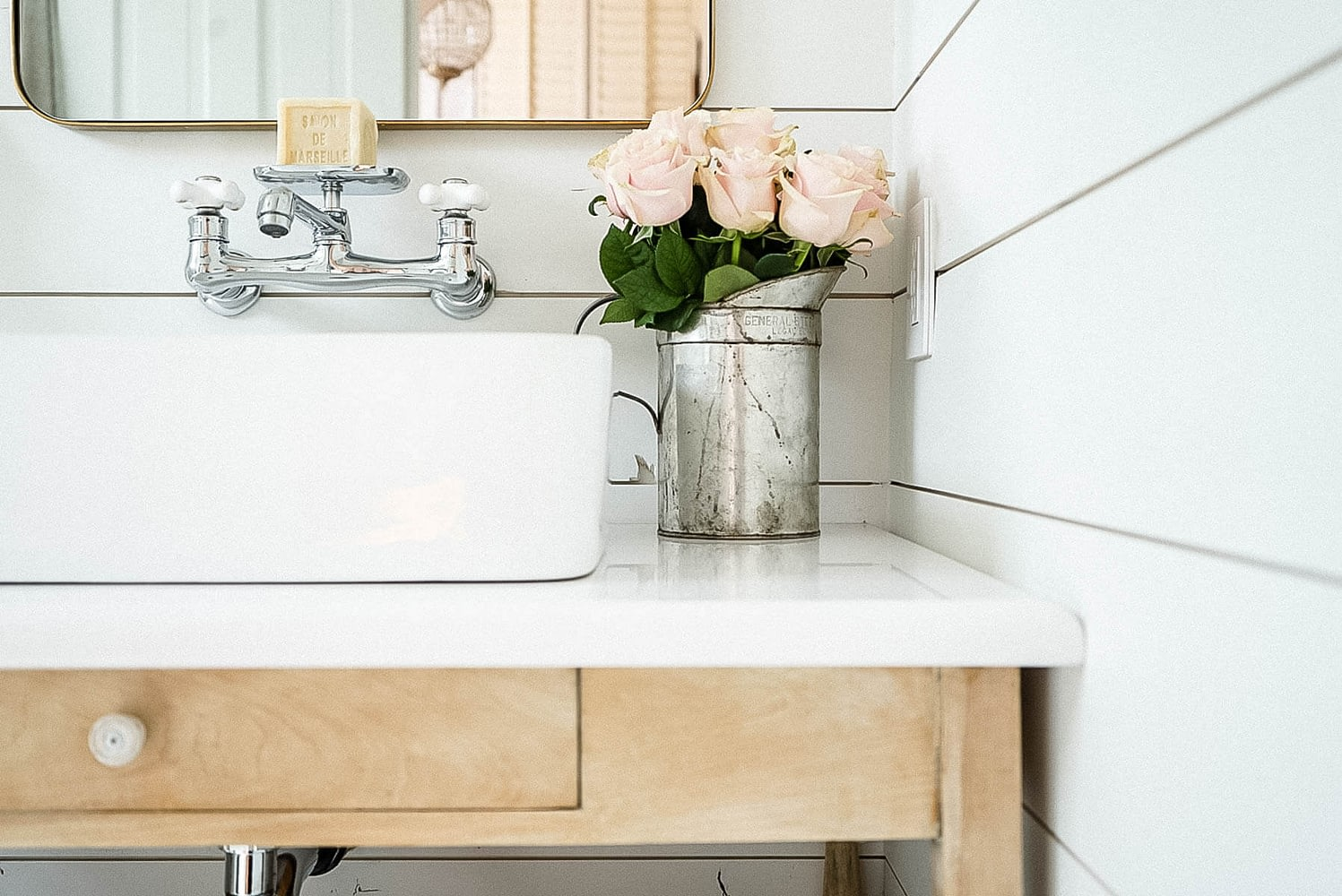 farmhouse bathroom with white shiplap and pink roses. Polished chrome faucet with a soap dish
