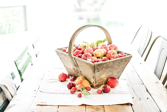 apples in a basket on a farmhouse table
