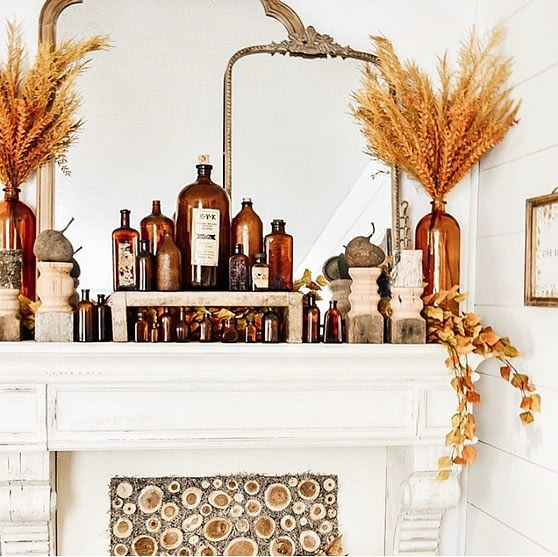 fall home decor amber bottle collection on faux fireplace mantle layered decor mirror pampas grass