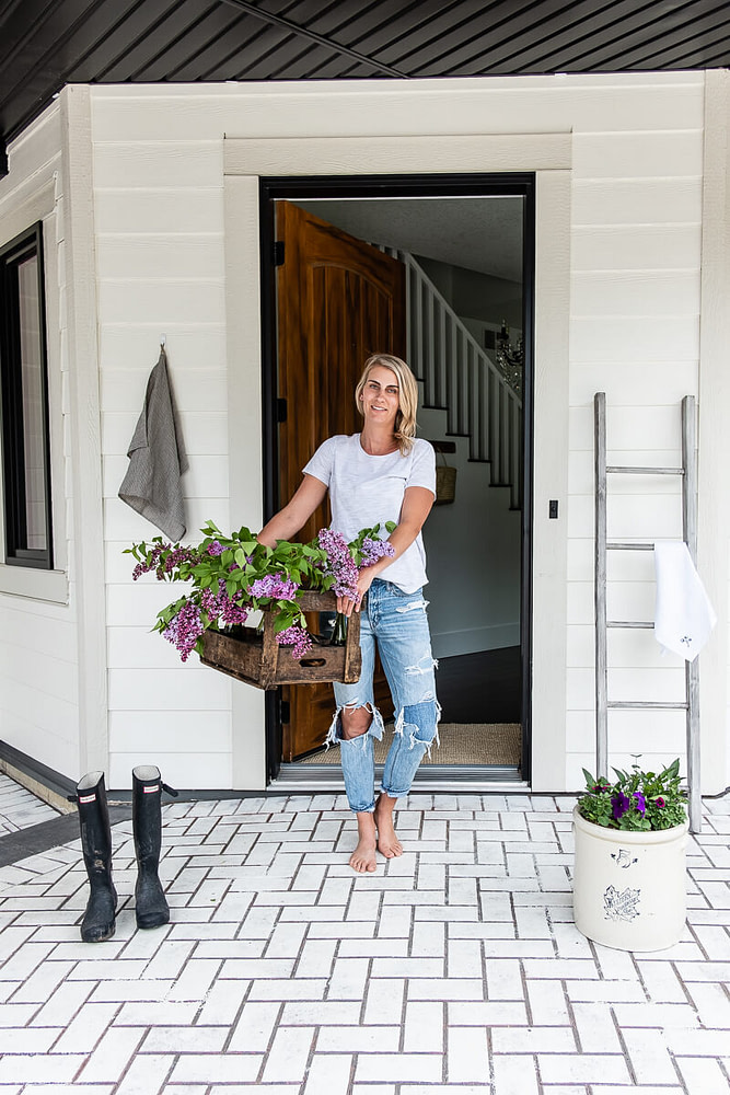 Britt holding wine crate with lilac trimmings