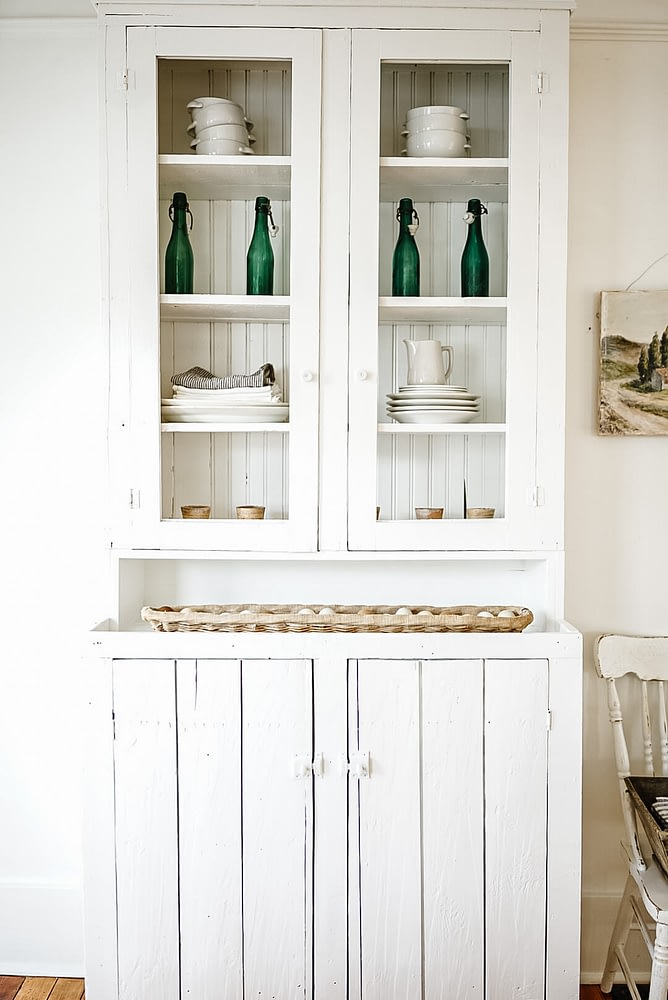 White kitchen hutch decor Belgian beer bottles linen ticking towels stacked dishes farm fresh eggs