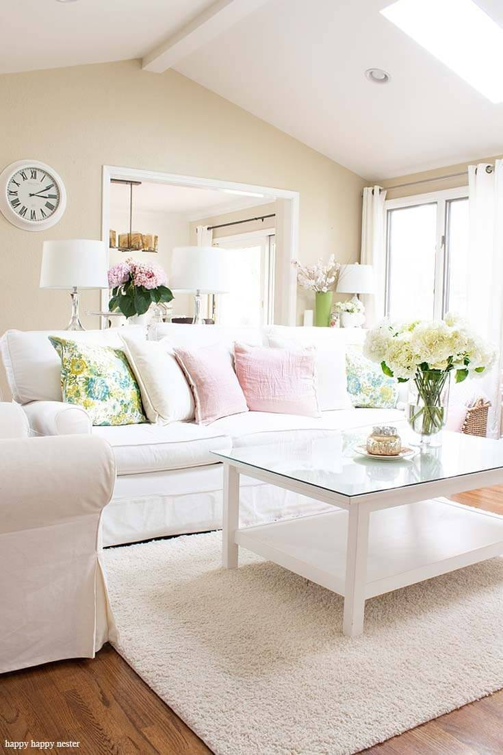white couch with floral centre pice and pastel colour palette to make a happy home